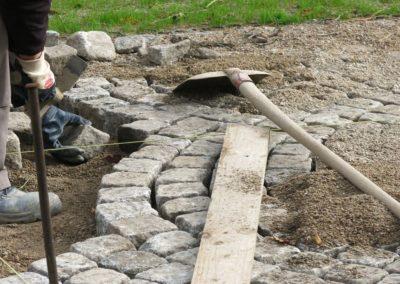 Handwerker verlegt Granit-Kleinpflaster in Segmentboegen