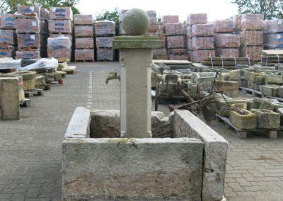 DeFries Aussenlager - Paletten mit antiken Mauerziegeln - grosser Natursteinbrunnen und Tröge