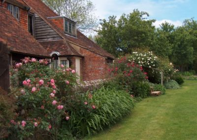 Altes englisches Cottage mit Natursteinmauer Rosenrabatten und Dacheindeckung aus antiken Roof-Tiles